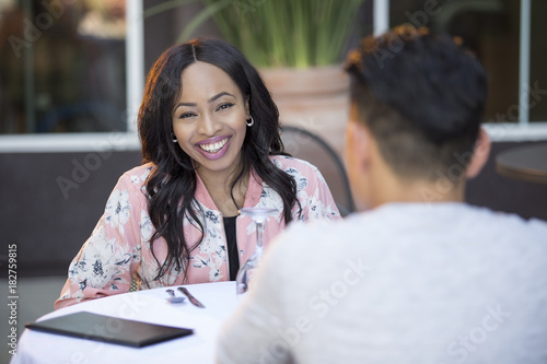 Black female on a blind date with an asian male at an outdoor restaurant Wallpaper Mural