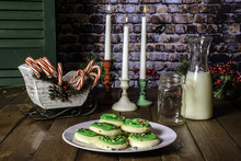 Sugar Cookies Decorated With Green Icing And Sprinkles On White Plate With Bottle Of Milk And Glass Mason Jar On Wood Table With Three Lit Candles And Candy Canes
