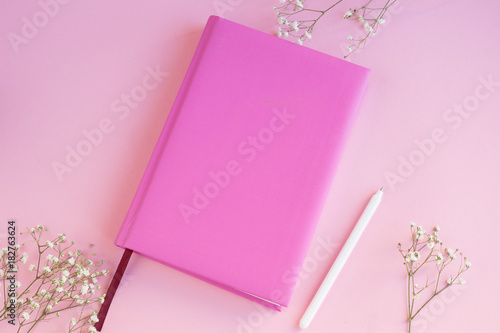 Fototapeta Table of a business woman with a pink notebook on a pink background with a white pen  obraz na płótnie