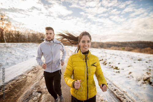 Poster Glisse hiver Charming young active runner girl jogging with her personal fit trainer on a snowy road in nature.