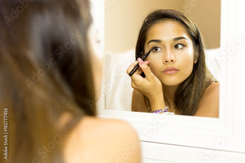 Fotografía Mixed race young woman with brush eye liner on looking in the mirror