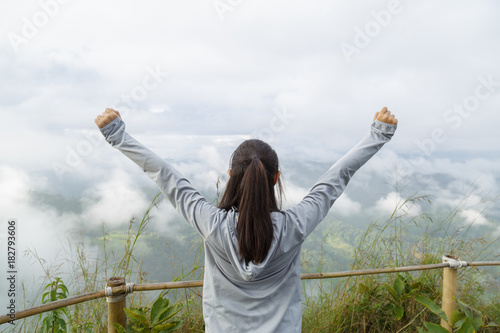 Asia girl relax and refresh on mountain background is a landscape of high mountains, white clouds and fog Canvas Print