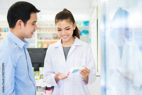 Photo  Female pharmacist holding medicine bottle giving advice to customer in pharmacy