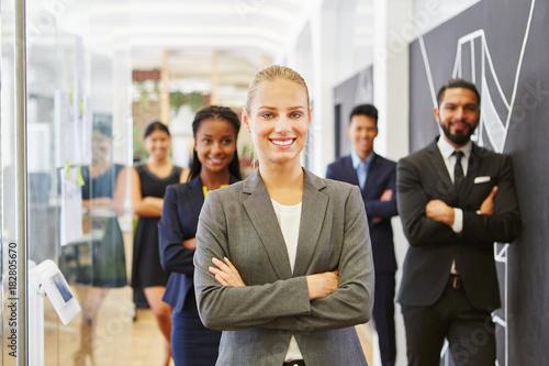 Erfolgreiche Geschäftsfrau vor ihrem Team Canvas Print