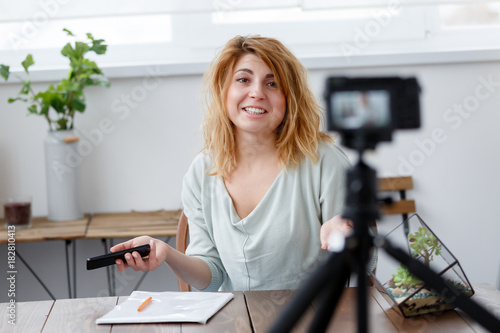 Fototapety, obrazy: Image of happy woman blogger at table with florarium.