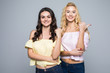 Two pretty women pointed on side over white background not isolated