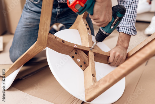 The man handyman is engaged in assembling the chair Fototapet