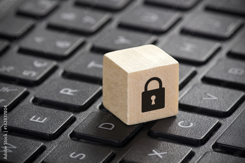 Fototapeta Wooden block with lock graphic on laptop keyboard. Computer security concept.