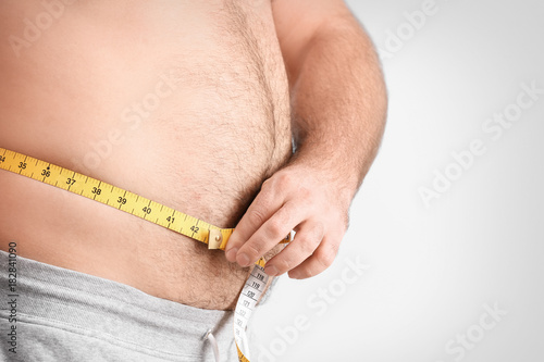 Overweight Man With Measuring Tape On Light Background Buy