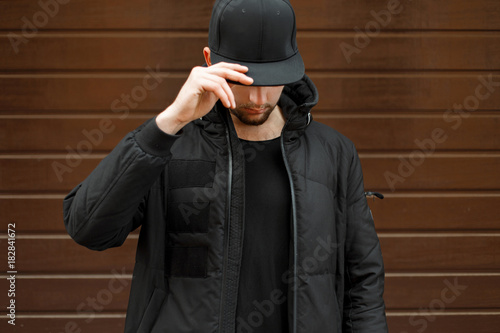 Fotografía  young man in a black fashionable baseball cap and a winter warm jacket posing on