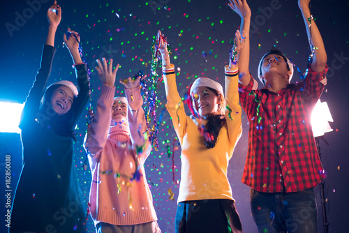 group of asian people celebrating new year party in night club with confetti