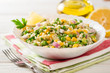 Salad with bulgur, green peas, corn, onion and greens on white rustic wooden table. Tabbouleh.