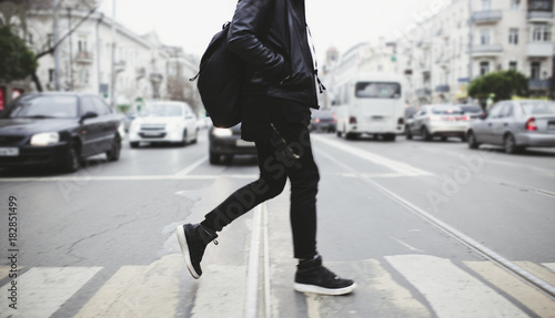 Photo  Modern young bearded man in black style clothes is walking at street