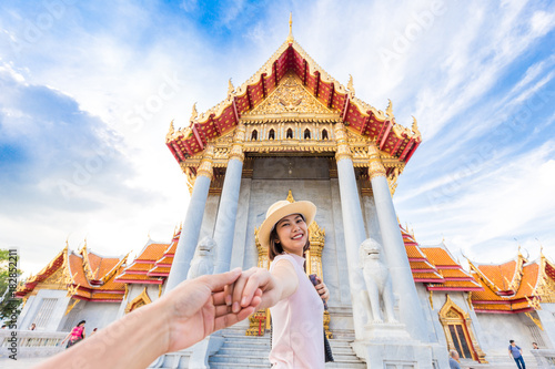 Deurstickers Bedehuis Asian tourist women in hat leading man hand to travel at marble temple