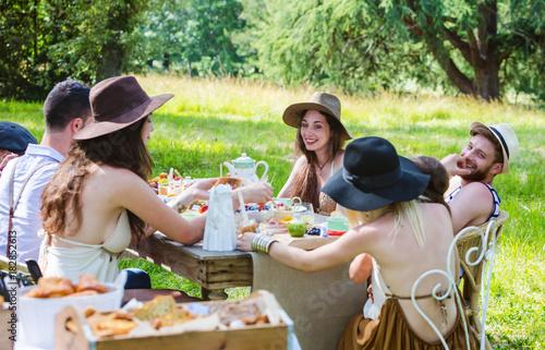 Fotografia  Groupe de jeunes personnes attablés lors d'un brunch à la campagne