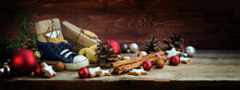 Wide Background For St. Nicholas Day, Children's Shoe With Sweets And Gifts On December 6th On Rustic Wood, German Christmas Consumption Called Nikolaus, Panoramic Format, Copy Space