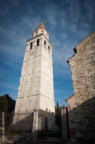 Photo Aquileia, campanile della Basilica di Santa maria Assunta con cielo azzurro di s