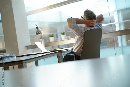 Fototapeta Businessman in office relaxing in desk chair