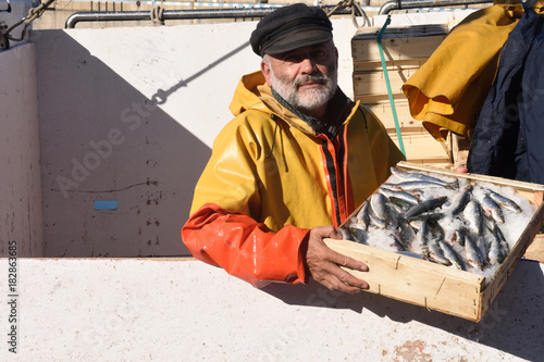 Obraz fisherman with a fish box inside a fishing boat - fototapety do salonu