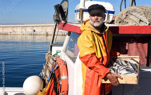 Fotografia, Obraz fisherman with a fish box inside a fishing boat