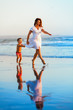 Happy family - mother, baby son have fun together, barefoot child run with splashes by water pool along sunset sea surf on black sand beach. Travel lifestyle, parents with kids on summer vacation.