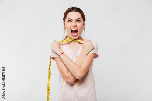 Fotografie, Obraz  Portrait of a young screaming girl strangling herself
