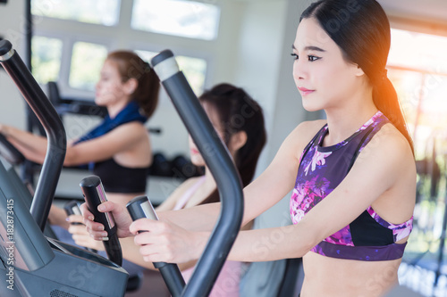 Spoed Foto op Canvas Fitness asian sport woman enjoy workout with treadmill in gym fitness center with group of people
