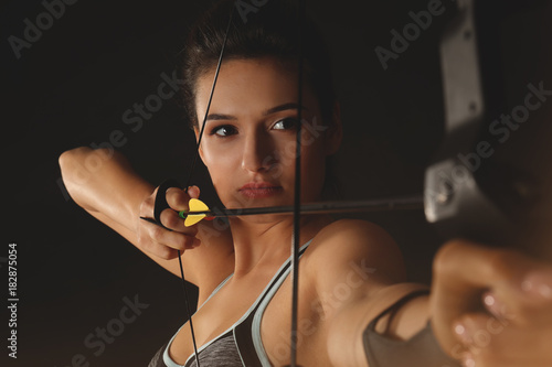 Sporty young woman practicing archery on dark background