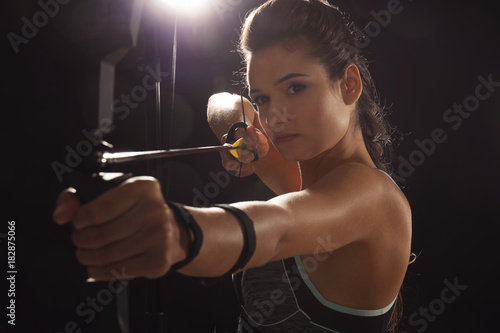Sporty young woman practicing archery on dark background Fototapete