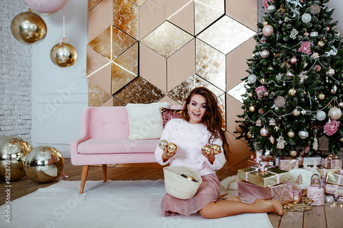 Fototapety, obrazy: The woman in a pink sweater decorates a Christmas tree.