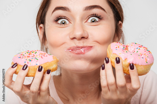 Fototapeta Close up portrait of a satisfied pretty girl eating donuts obraz