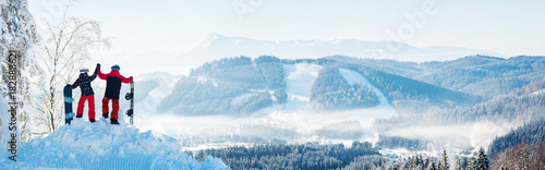 obraz dibond Winter panorama of the Carpathians mountains landscape and forests in a white haze. In the side couple high fiving each other on top of a snowy mountain, resting after snowboarding at ski resort