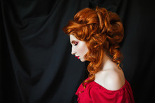 Beautiful Red-haired Girl In Red Dress Posing On Black Background. Portrait Of A Woman With Red Hair