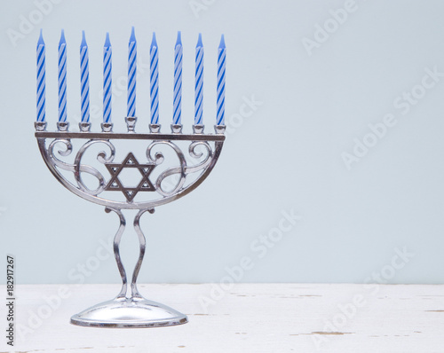 Fotografie, Obraz  Hanukkah Menorah with a Simple Blue Background on a Distressed Wooden Table