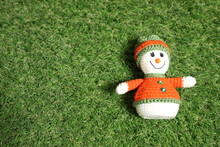 Little Toy Christmas Snowman On Green Grass Background