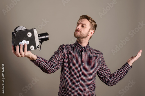 Fototapeta Young attractive cameraman in a plaid shirt takes himself off to an old movie camera