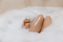Close Up Photo Of Young Sexy Woman With Straight Naked Body And Clean Legs Lying And Relaxing In White Foam Bath Tub With Candles Around In Light Bathroom, Drink Alcohol From Wine Glass Indoors.