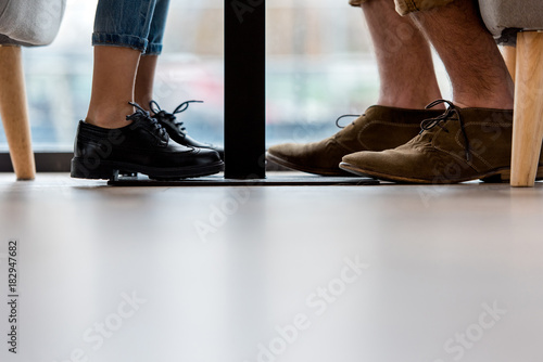 Cropped Image Of Father And Daughter Legs Under Table