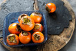 Fresh persimmon in a glass plate on a wooden table. Copy space