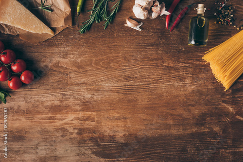 Fotomural top view of row pasta and fresh ingredients on wooden table with copy space