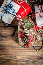 Christmas, New Year's Concept. Mason Jar With Christmas Decorations, Fir Cones, Artificial Snow, Candy Cane And Fir Branch. On A Wooden Table Background. Copy Space