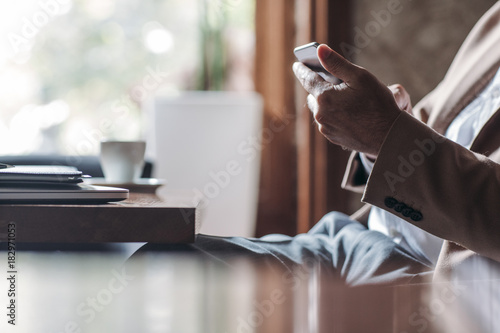 Fototapety, obrazy: Businessman Typing on Cell Phone