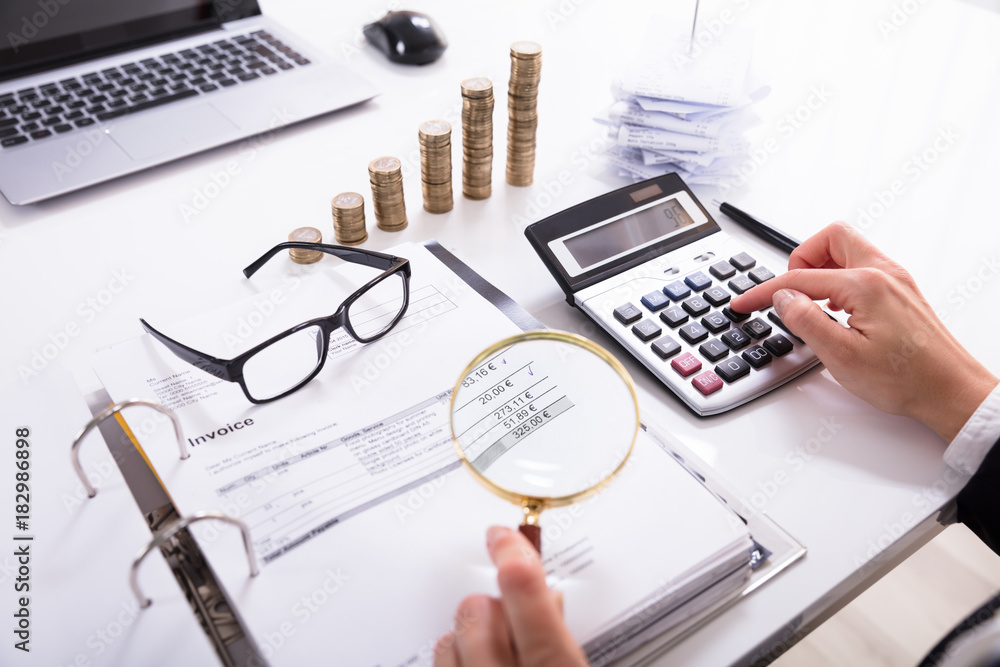 Fototapeta Businesswoman Checking Invoice With Magnifying Glass