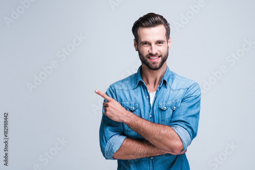 Have you seen this? Handsome young man pointing away and looking at camera with smile while standing against white background