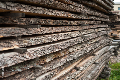 Fotografía  Folded wooden brown and gray planks in a sawmill
