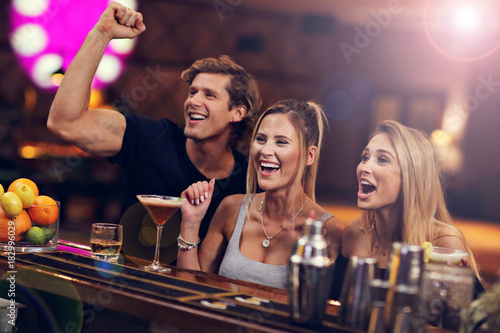 Group Of Friends Enjoying Drink in Bar Wallpaper Mural