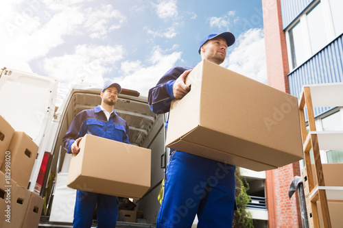 Close-up Of Two Delivery Men Carrying Cardboard Box Fototapet