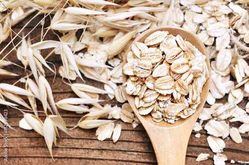 Oat groat in wooden spoon, oatmeal grain for healthy diet on