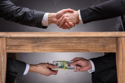 Fotomural Businesspeople Shaking Hands And Taking Bribe Under Table