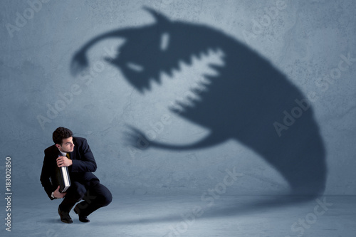 Photo Business man afraid of his own shadow monster concept